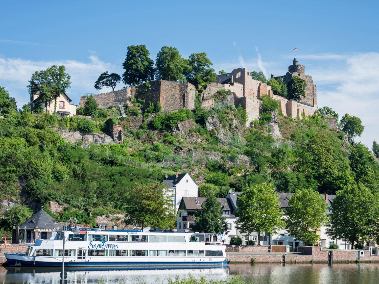 Blick auf die Saar mit der Saarburg auf der Höhe und einem Schiff an der Schiffsanlegestelle