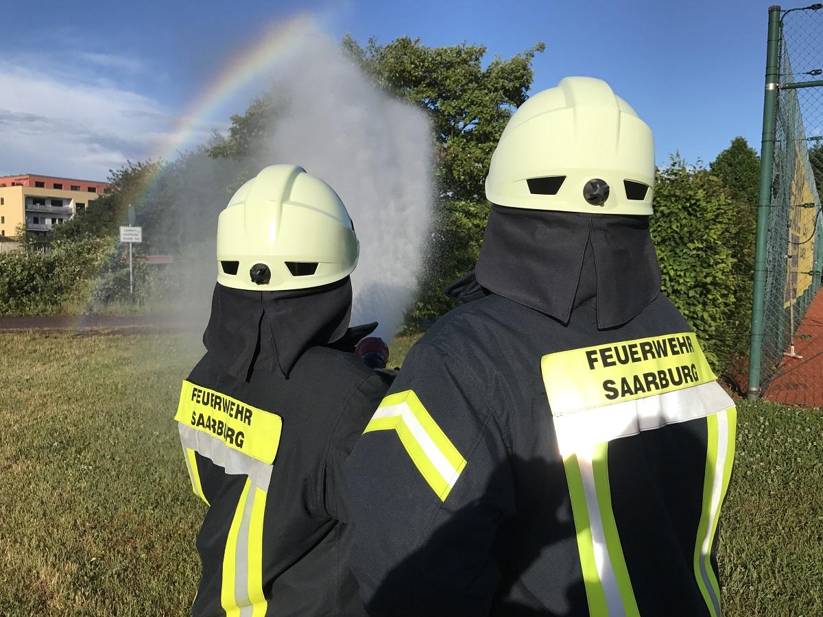 Feuerwehr Saarburg, zwei Feuerwehrmänner löschen mit Wasser Brand