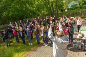 Französische Kinder tanzen und singen ein Begrüßungslied für die deutschen Freunde