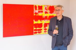 Oliver Christmann vor farbenfrohem roten Bild